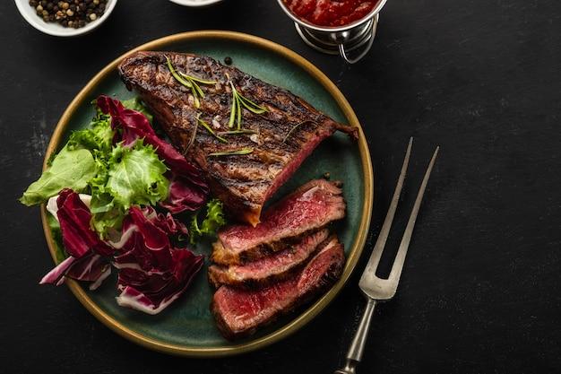 暗い背景上に新鮮なサラダと牛肉のグリルバーベキューをスライス