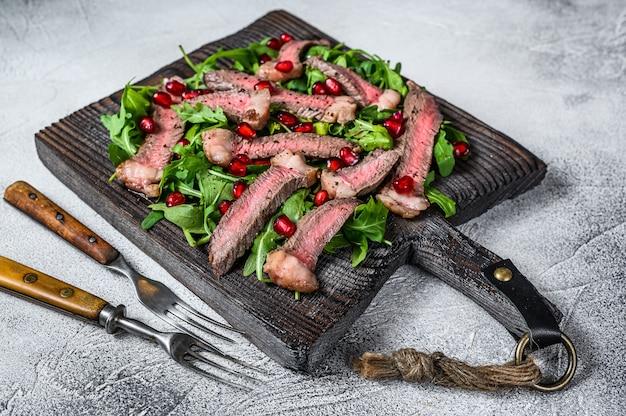 ルッコラを添えたスライスしたビーフステーキのグリルは、素朴なまな板の上にサラダを残します。白色の背景。上面図。