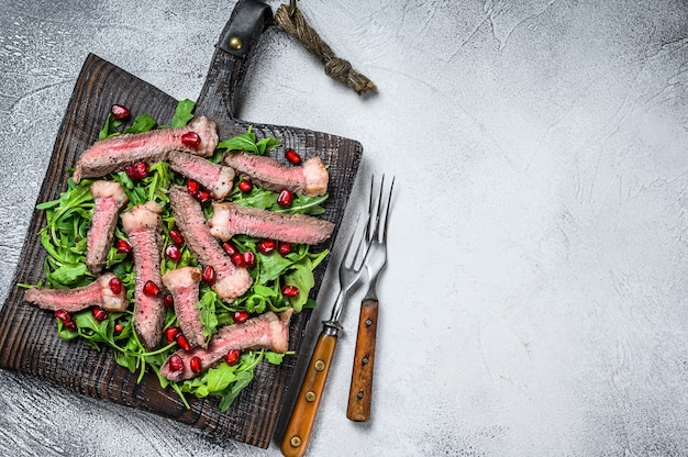 Sliced grilled beef steak with arugula leaves salad on rustic cutting board