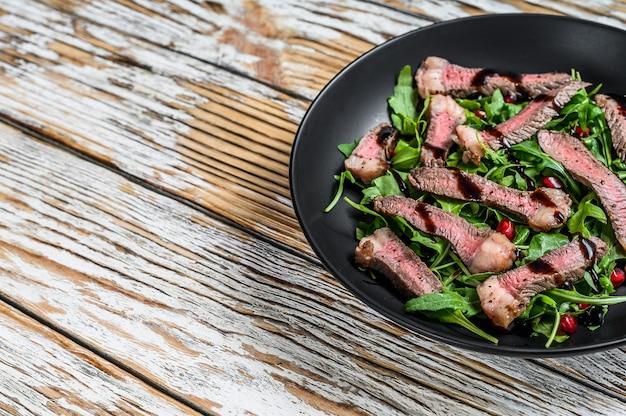 ルッコラの葉のサラダを添えたスライスしたグリルビーフステーキ。白い木製の背景。上面図。スペースをコピーします。