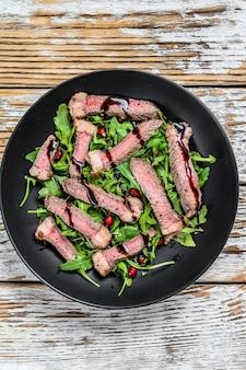 Sliced grilled beef steak with arugula leaves salad.