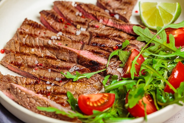 Sliced grilled beef steak with arugula and tomato salad in white plate, dark background, close-up.