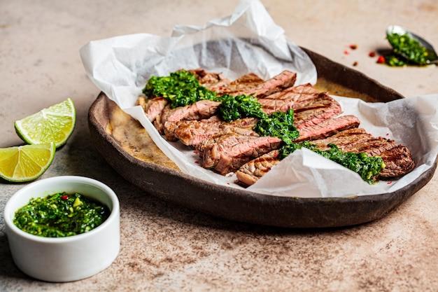 Sliced grilled beef steak with chimichurri sauce on a dark dish, dark background.