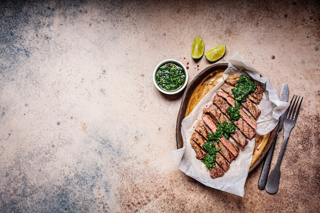 Sliced grilled beef steak with chimichurri sauce on dark dish, top view, dark background.