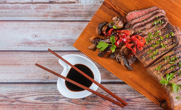 Sliced grilled beef with mushrooms on cutting board.