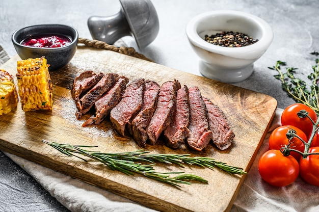 Sliced grilled black angus marbled beef steak on a wooden chopping board. gray wall. top view.