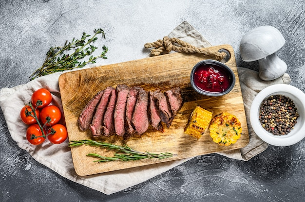 Sliced grilled black angus marbled beef steak on a wooden chopping board.