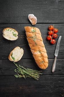 검은색 나무 테이블 배경에 마늘과 허브 세트가 있는 얇게 썬 구운 빵, 평면도