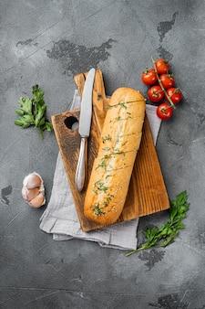 회색 돌 탁자 배경에 마늘과 허브를 넣은 얇게 썬 구운 빵, 텍스트 복사 공간이 있는 평면도