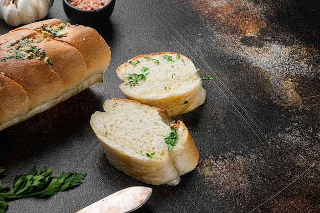 오래된 어두운 소박한 테이블 배경에 마늘과 허브 세트가 있는 얇게 썬 구운 빵, 텍스트 복사 공간