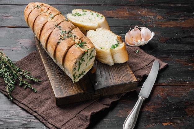 오래된 어두운 나무 테이블 배경에 마늘과 허브 세트를 곁들인 구운 빵