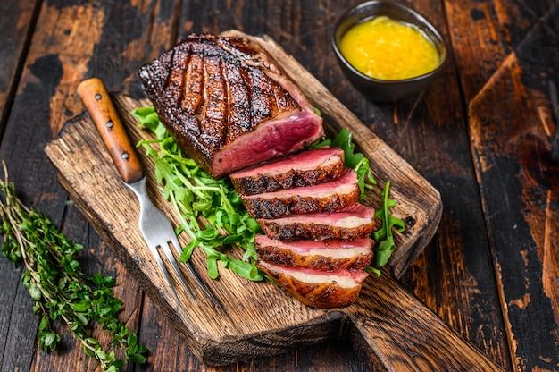 구운 오리 고기 가슴살 스테이크 슬라이스. 어두운 나무 배경입니다. 평면도.