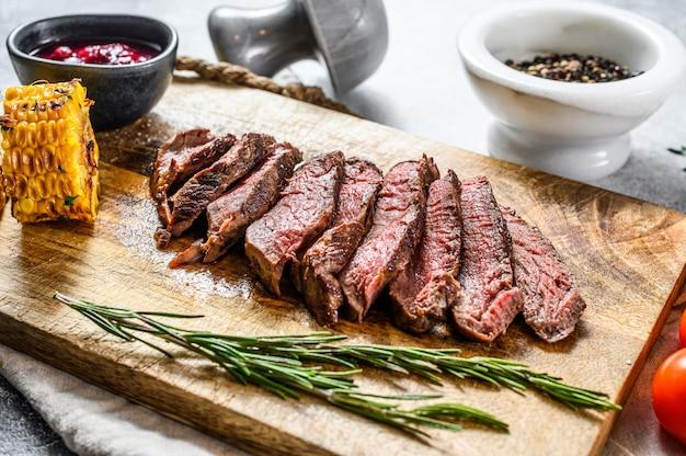 Sliced grilled filet mignon steak on a wooden chopping board. beef tenderloin.