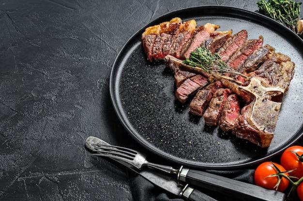 구운 피렌체 스테이크 슬라이스. t 뼈 고기 쇠고기. 검정색 배경. 평면도. 공간을 복사하십시오.