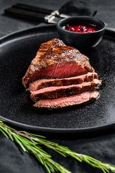 Sliced grilled marbled beef steak. beef tenderloin. black wall. top view