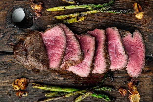 Нарезанный на гриле стейк из мраморного мяса нарезанный нарезанный филе миньон с луком и спаржей на деревянной сервировочной доске