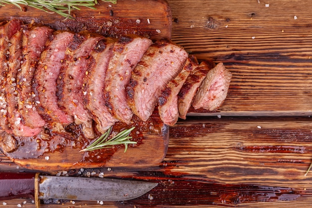 Sliced grilled meat beef steak ribeye with spices on rustic wooden cutting board