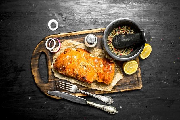 향신료와 함께 보드에 구운 고기를 슬라이스. 검은 칠판에.