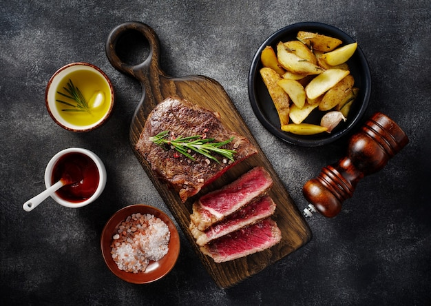 회색 배경에 나무 보드에 소스와 감자와 구운 된 고기 스테이크 뉴욕 striploin 슬라이스. 평면도.