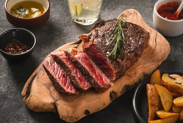 회색 배경에 나무 보드에 소스와 감자와 구운 된 고기 스테이크 뉴욕 striploin 슬라이스.