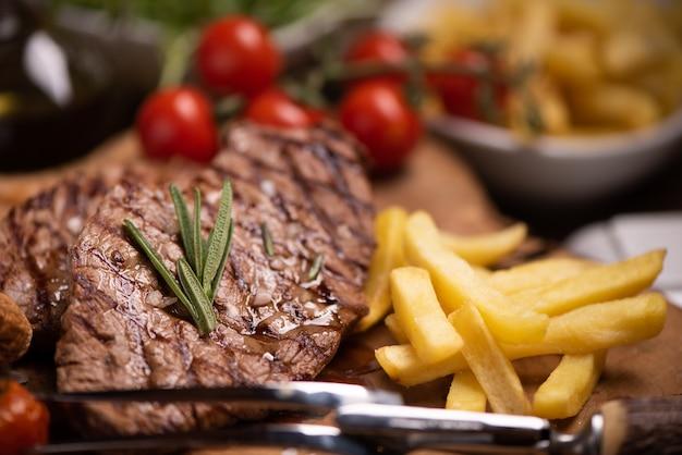 Нарезанный на гриле стейк из говядины средней прожарки с картофелем фри крупным планом