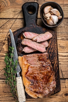Sliced grilled new york strip beef meat steak or striploin on a wooden board