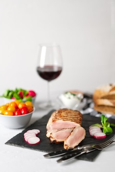 Sliced grilled pork fillet with fresh tomatoes and raddish served with glass of red wine. soft focus photo.