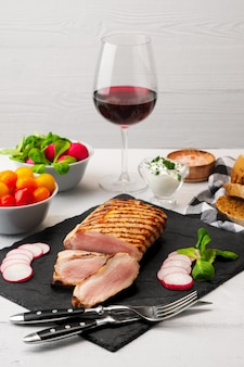 Sliced grilled pork fillet with fresh tomatoes and raddish served with glass of red wine.
