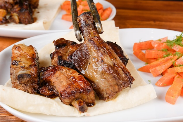 Sliced grilled pork ribs on pita bread with grilled carrots on a white plate on a wooden background.