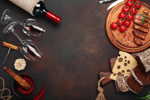 Нарезанные на гриле свиные стейки на разделочной доске с помидорами черри, сыром, хлебом, чесноком и розмарином