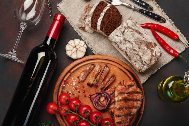 Sliced grilled pork steaks with bottle of wine, wine glass, corkscrew, knife, fork, black bread, cherry tomatoes, garlic, onion and rosemary on rusty background