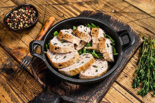 Sliced grilled pork tenderloin steak in a pan. wooden background. top view.