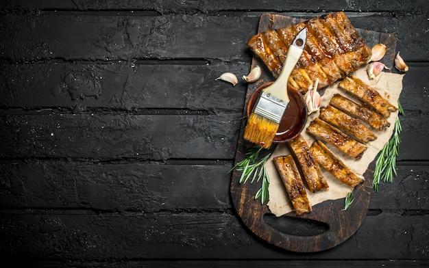 Нарезанные ребрышки на гриле с соусом на деревенском столе.