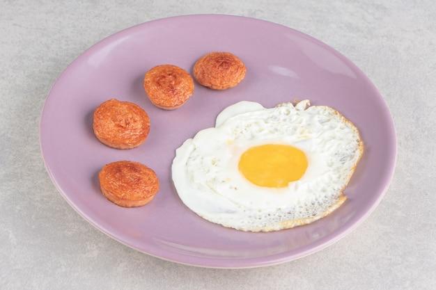 Нарезанные колбаски гриль и жареное яйцо на фиолетовой тарелке.