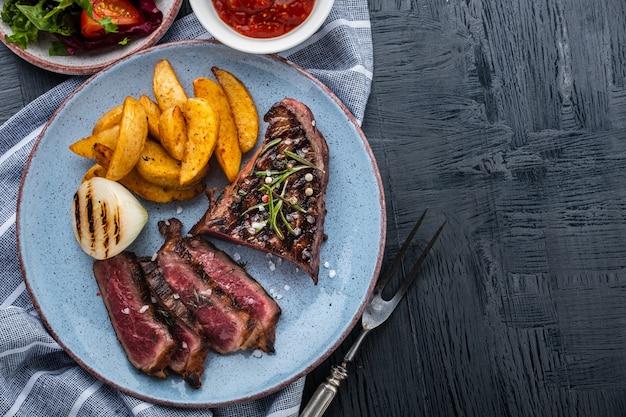 ステーキ肉のグリル。ポテトとフライドオニオンのビーフステーキミディアム