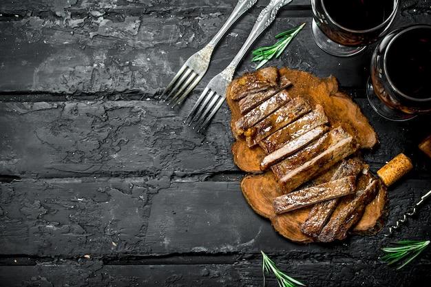 Нарезанный стейк на гриле с вином. на черной деревенской поверхности.