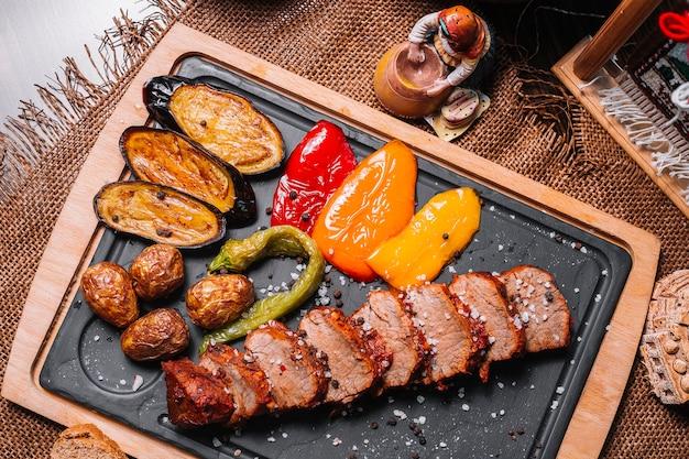 Sliced grilled steak on the wooden board bell pepper potato eggplant salt top view