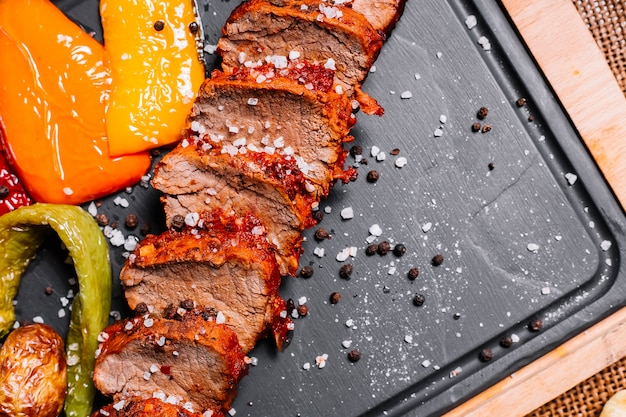 Sliced grilled steak on the wooden board pepper tomato sea salt top view