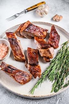 정육점 칼로 구운 송아지 고기 짧은 갈비 고기. 검은 배경. 평면도.