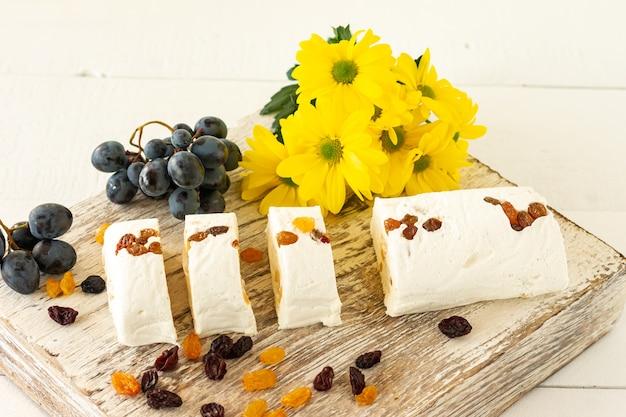 접시에 견과류와 말린 과일을 곁들인 얇게 썬 할바는 흰색 테이블에 꽃과 과일과 함께 제공됩니다.