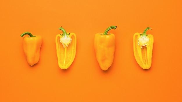 Нарезанные половинки оранжевого перца на оранжевом фоне. вегетарианская пища.