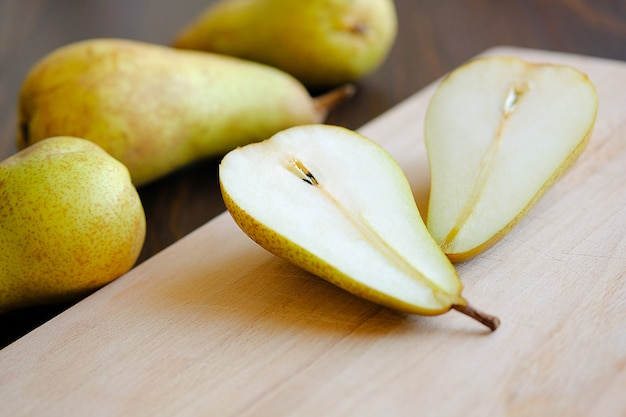 Sliced halves or slices of fresh sweet ripe yellow and green pears, next whole pears and cutting kitchen board