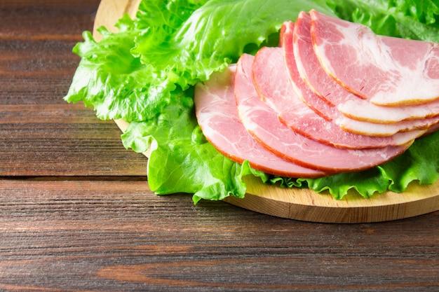 Sliced ham fresh green lettuce leaves on a round cutting board.