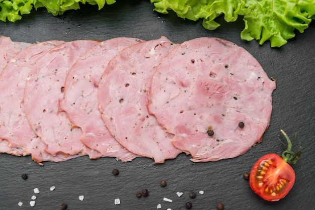 Sliced ham sausage on a stone surface