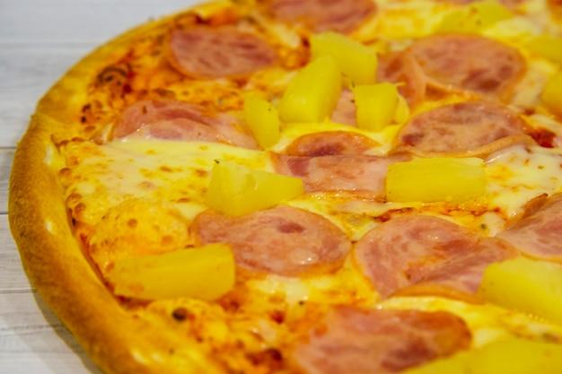 Нарезанная гавайская пицца с ветчиной и ананасом на светлом деревянном столе. итальянская кухня. сладкая пицца