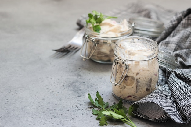 Sliced herring in sour cream sauce served in a glass jar.