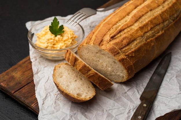 木製のまな板で自家製パンをスライスしました。チーズサンドイッチを作る。閉じる