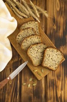 Нарезанный домашний хлеб на разделочной доске на коричневом деревянном фоне. вид сверху. расположение вертикальное.