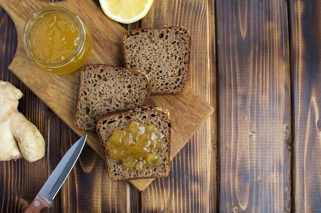 茶色の木製の背景のまな板に生姜ジャムとスライスした自家製パン。上面図。コピースペース。