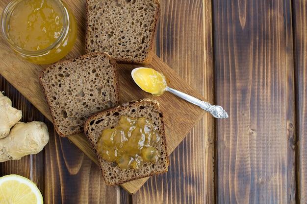 Нарезанный домашний хлеб с имбирным вареньем на разделочной доске на коричневом деревянном фоне. вид сверху. копия пространства.